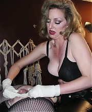 Submissive sissy in fishnets anally trained by mature blonde Mistress in latex pants and big strapon cock